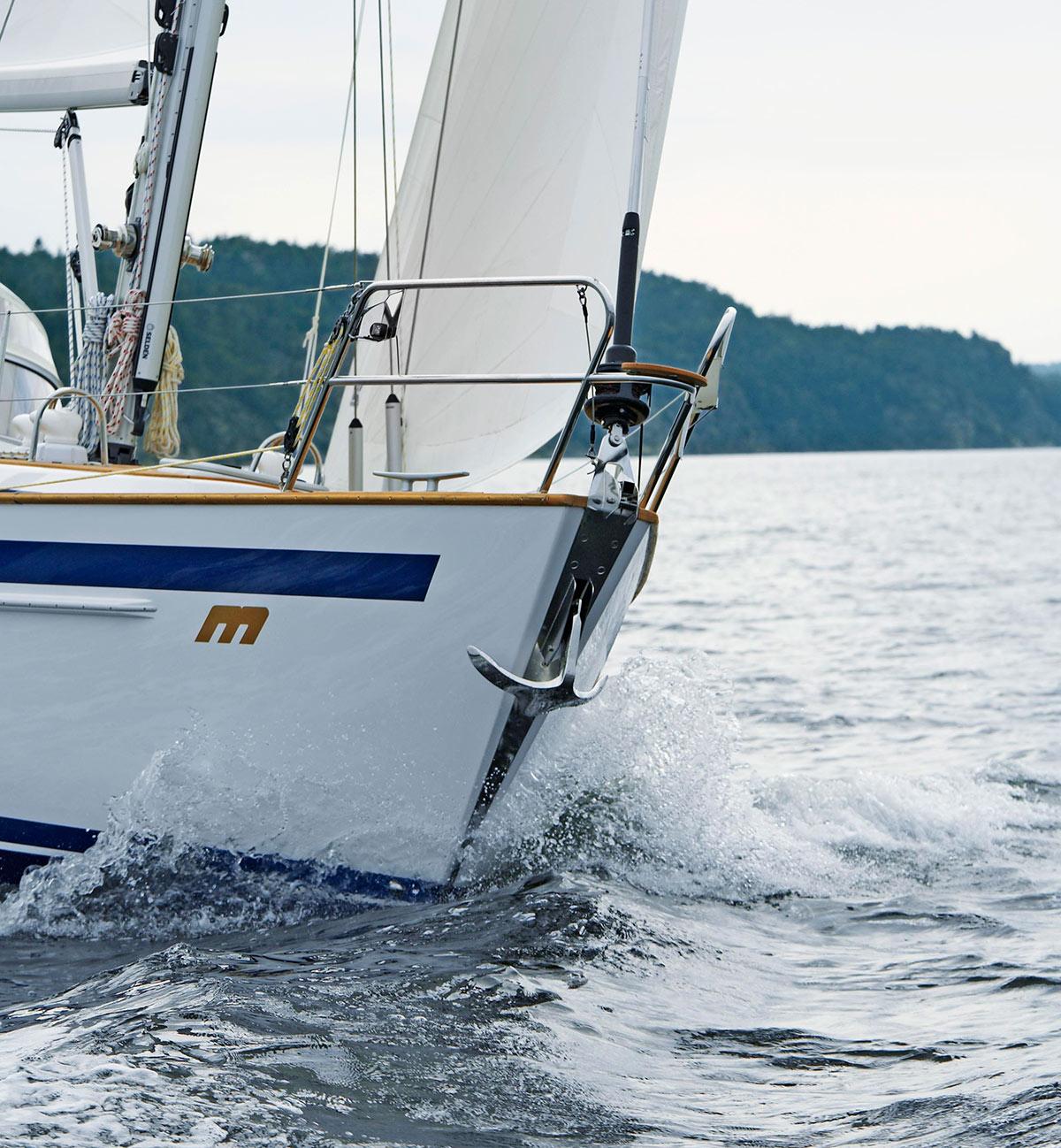 en segelbåt ute till havs med ett dragg hängandes i fören